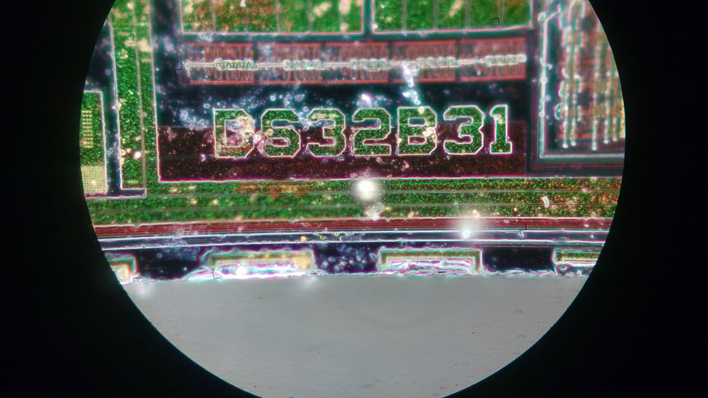 "A close-up of the DS32B31 marking in the bottom-center of the die. It's unclear what the ""B"" stands for. Several large pieces of dust are visible."