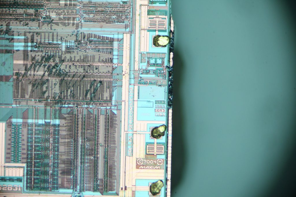 The edge of the chip with many human-readable markings (e.g. Dallas Semiconductor, Maxim, etc.).