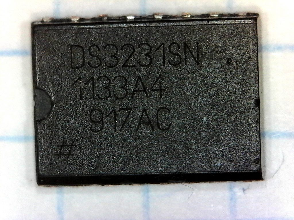 "The exterior of the chip's package. It has the markings ""DS3231SN"" on the first line, ""1133A4"" on the second, ""917AC"" on the third, and a ""#"" sign on the fourth."
