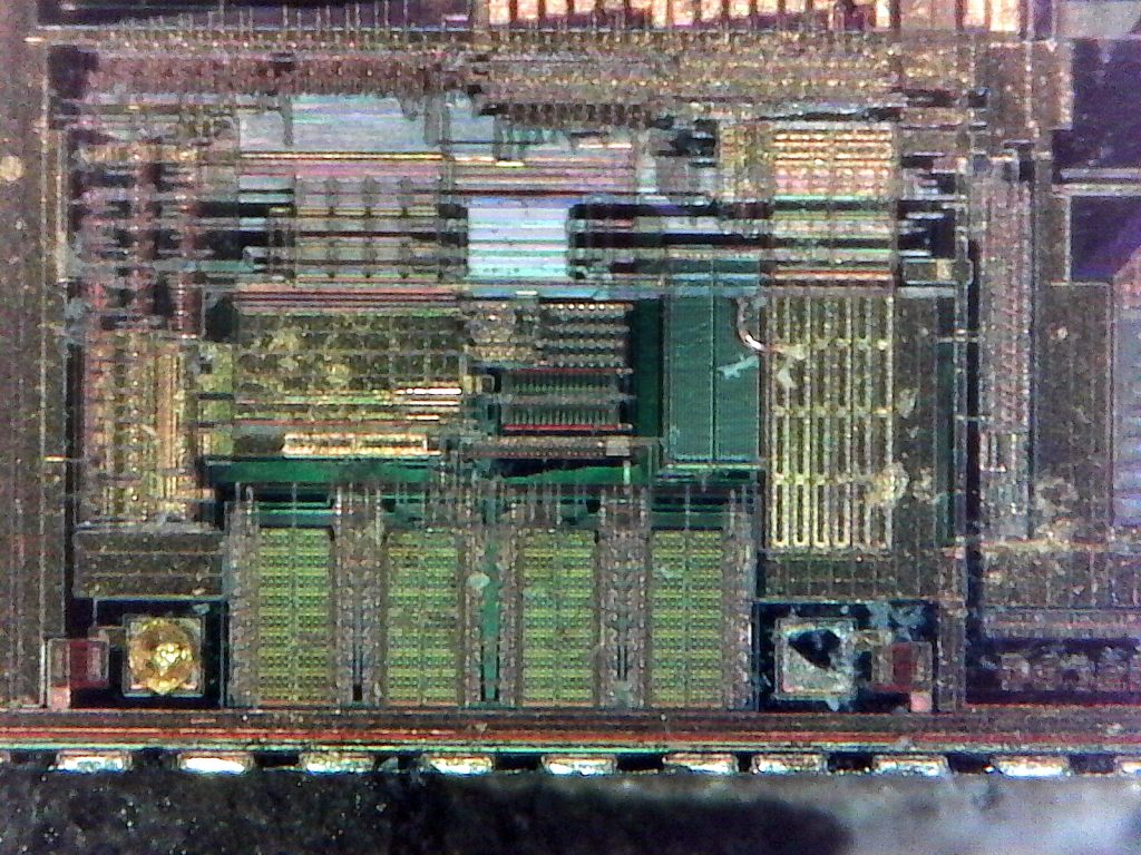 "A different region of the chip, to the left of the ""DS3231"" marking mentioned earlier. Two bonding pads are visible, one with a bit of the gold bond wire remaining attached, while the other has had the wire removed."