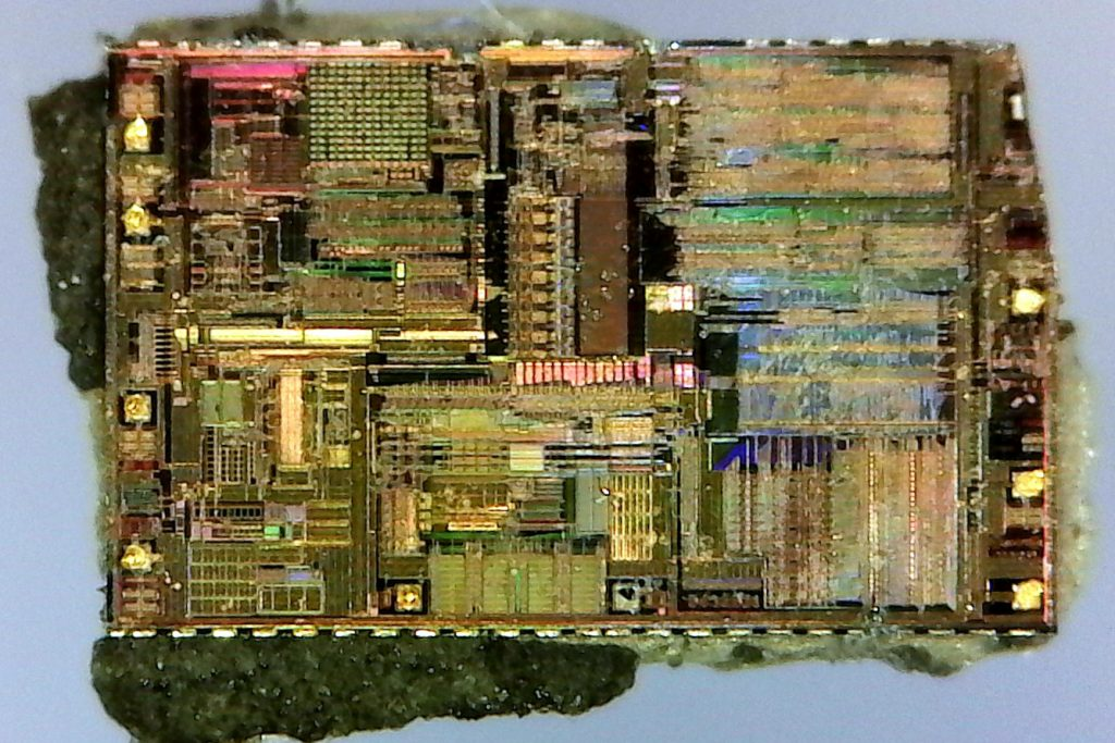 A photo showing the whole die. Ten bonding pads are visible, several still with the remains of gold wires still attached. A small area in the upper-right of the die has been snapped off while removing the chip from the packaging, and small pieces of packaging are still stuck to the outer edges of the die. Several distinctly different regions of the chip are visible, clearly with different functions.